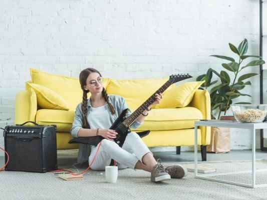 Woman playing electric guitar at home